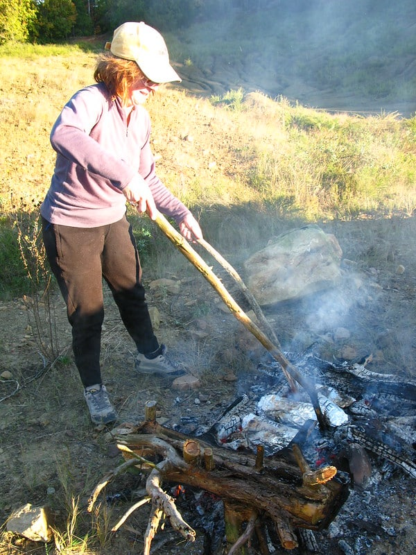 using sticks to turn food over campfire