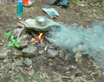 campfire cooking on top of rock