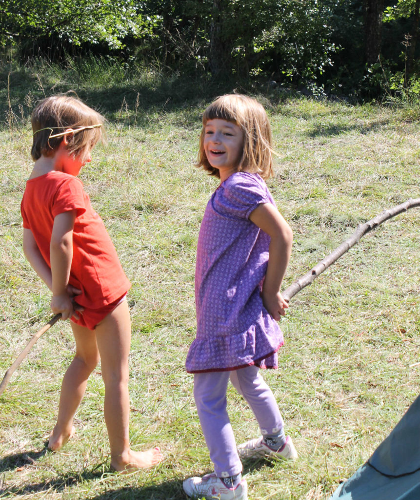 kids playing with sticks while camping