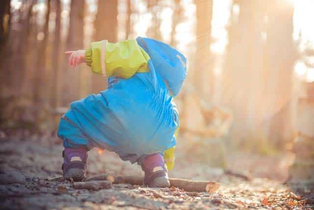 toddler playing in rain suit