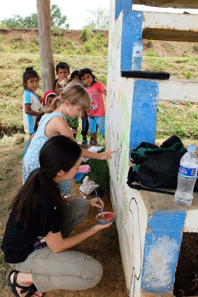 painting a mural in a Peruvian village