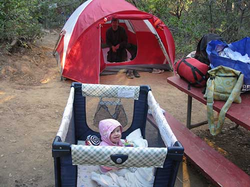 baby in a portable play pen while camping