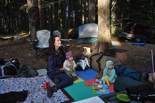 sitting on a picnic blanket while camping with babies