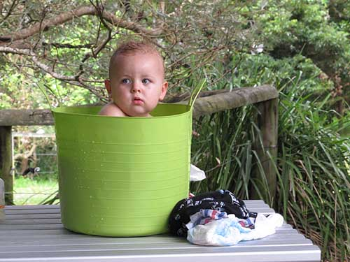 baby taking a bath in a bucket while camping